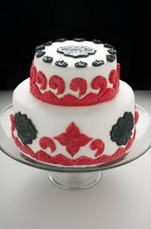Double tiered cake with white red and black fondant decorations photo