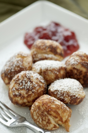 Freshly made Danish breakfast ebelskivers with strawberry preserves and powdered sugar