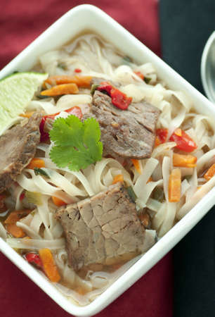 Hot Asian inspired noodle soup with spicy beef and vegetables photo