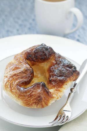 Fresh golden lemon croissant on a white plate 版權商用圖片