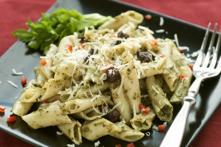 black dish: Black plate with penne pasta, sausage and pesto