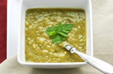 파 슬 리 장식과 녹색 완두콩 수프의 사각 흰색 그릇