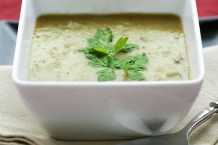 Square white bowl of green pea soup with parsley garnish