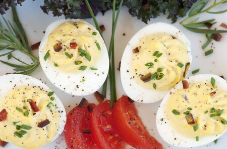 piped: Decorative piped filling in deviled eggs with vegetable and herb garnish