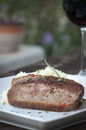 Slice of homemade meat loaf with mashed potatoes and wine sauce photo