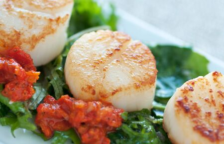 Fresh seafood dish on sauteed greens and red pepper sauce