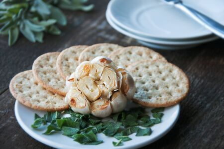 Appetizer of roasted garlic with crackers and herbs Stockfoto