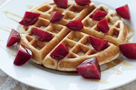 Golden round waffle with hone and fresh pluots 版權商用圖片 - 17654758