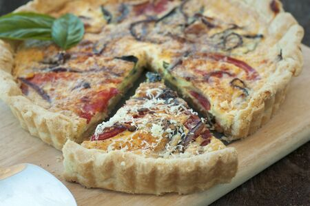 Golden crusted quiche with heirloom tomatoes, onions and herbs photo