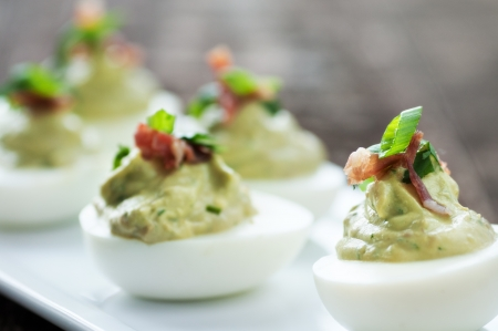 Fancy green deviled egg appetizer with garnish