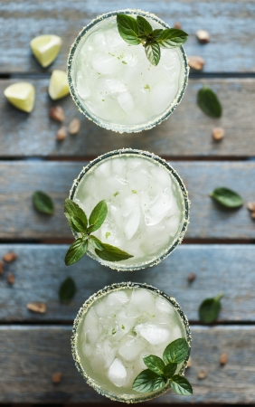 cocktail glasses: Ice cold beverage with lime and mint Stock Photo