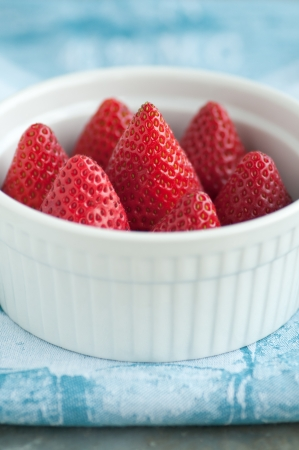 White ramekin of fresh ripe strawberries
