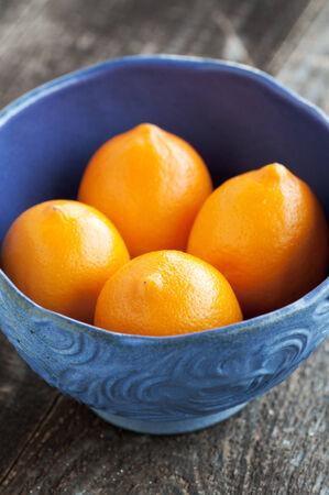 Purple ceramic bowl of fresh Meyer Lemons Фото со стока - 27734782
