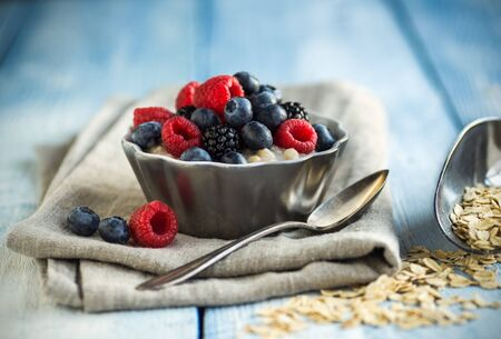 Bowl of oatmeal porridge with mixed berries Reklamní fotografie