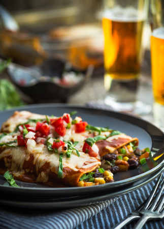 Spicy black bean and corn enchiladas with sauce and cheese