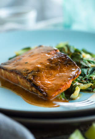 salmon filet: Salmon filet roasted with red curry sauce and sauteed greens