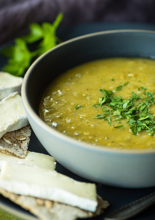 Fresh split pea soup with crackers and brie cheese