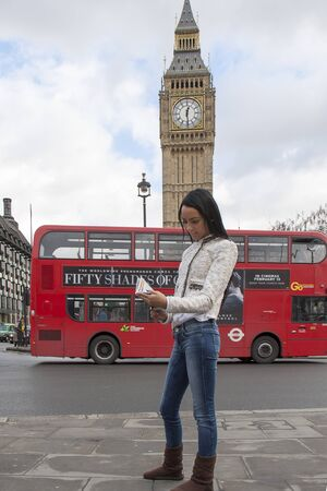 travel guide: A young tourist reading a travel guide in London by Big Ben Editorial
