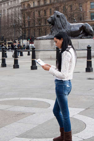 travel guide: A young tourist reads a travel guide at Trafalgar Square, London