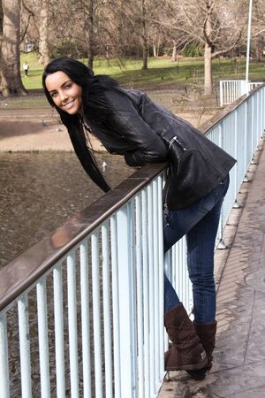 olive skin: An attractive young woman leaning over a bridge Stock Photo
