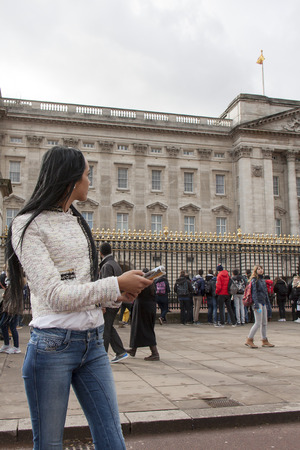 buckingham palace: A pretty tourist consults a travel guide at Buckingham Palace Editorial