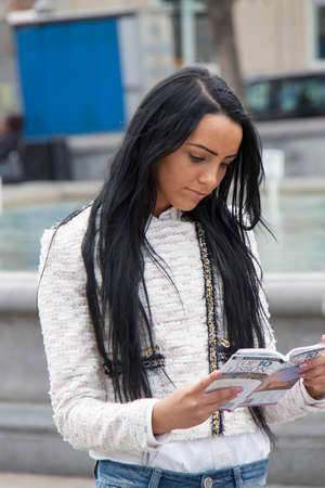 travel guide: A young woman reads a travel guide in a city centre Stock Photo