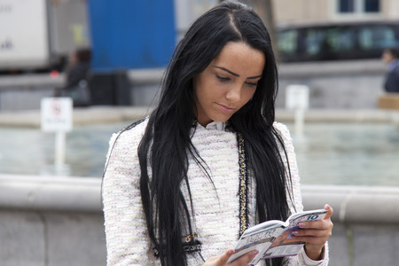 travel guide: A young woman reads a travel guide in the city centre
