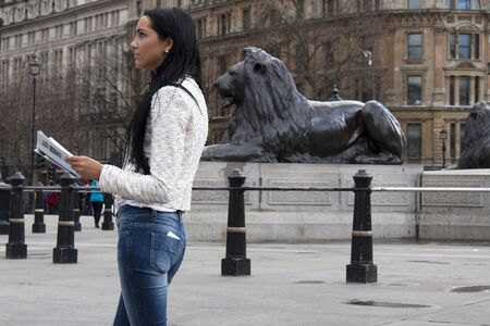 travel guide: A young woman reads a travel guide in London Stock Photo