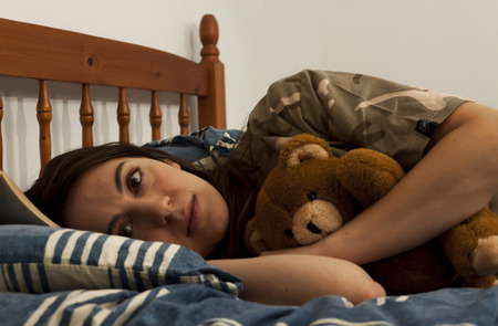 insomniac: A young woman awake in bed with a teddy bear