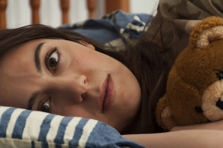 A young woman hugs a teddy bear in bed Stock Photo