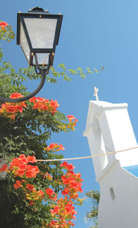 lamp, church with steeple and flowers in the greek islands photo
