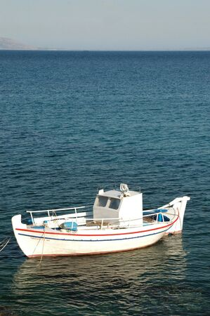a greek fishing boat with the island of naxos in the distance photo