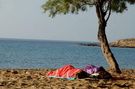 2 people sleeping on the beach
