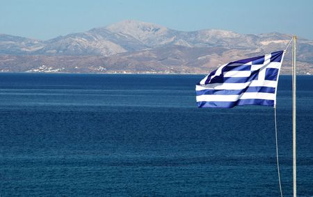 flag of greece waving in the wind with the island of naxos visible in the background