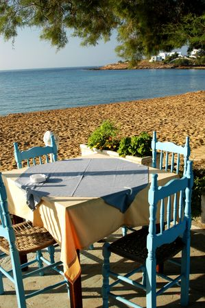 seaside dining in the greek islands with typical greek building in the background