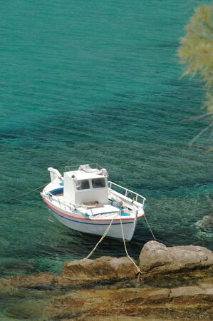 a greek fishing boat anchored by the rocky coast photo