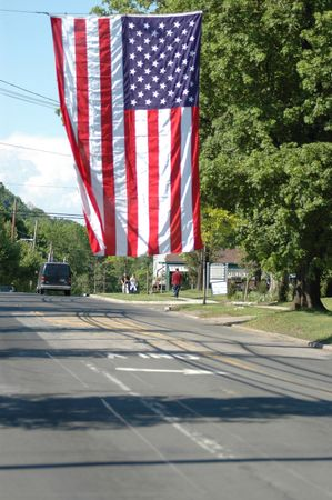 vj: a huge flag hanging on a main street in a small town on memorial day in the usa