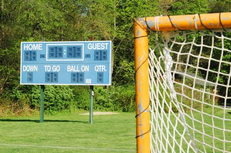 a goal and scoreboard on a small town sports field photo