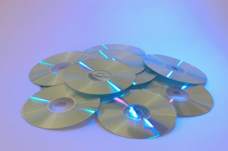 cd roms laid out with a blue purple background Imagens