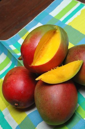 yellowish green: mangoes on a table cloth with one sliced open