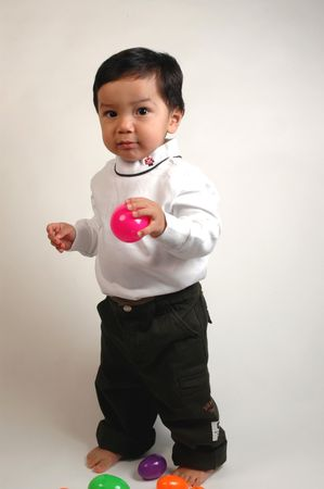hispanic boy playing with brightly colored balls