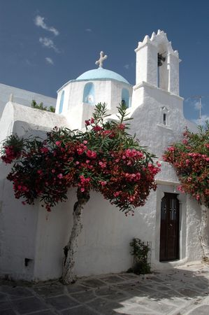 a greek church with a beautiful dome and a flowering tree in the greek islands photo