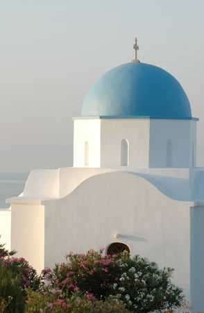 a church in the greek islands overlooking the sea with azalea bushes as the sun comes up photo