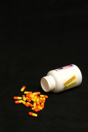 prescribed: colorful prescription pills falling out of the bottle Stock Photo