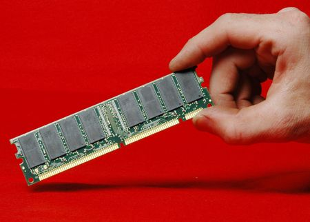 a hand holding a memory dimm card photo