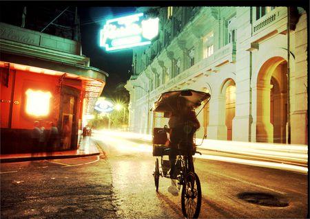 a vendor on a three wheel bike going past the famous floridita bar in old havana, cuba Banco de Imagens