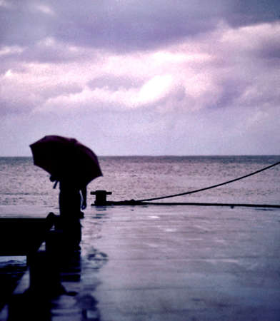 solace: a dreamy shot of a person on a pier with an umbrella