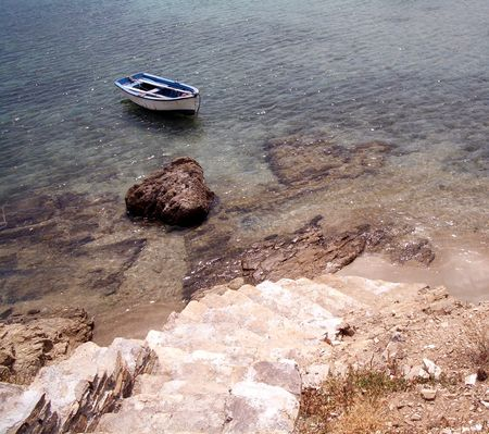 stone tile steps leading to the shore with an old row boat in the greek islands photo