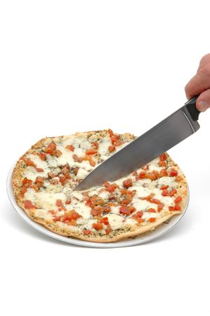 slicing: hand slicing a whole margherita pizza isolated on a white background with a reflection of pizza on the knife Stock Photo