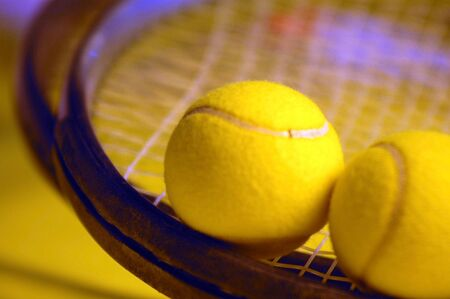 tennis rackets with focus on the top fuzzy hairs of the ball on the left and the strings between the two balls in front for effect